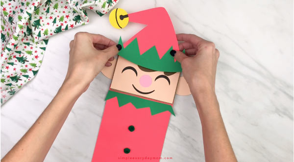 hand gluing hat to paper bag elf craft