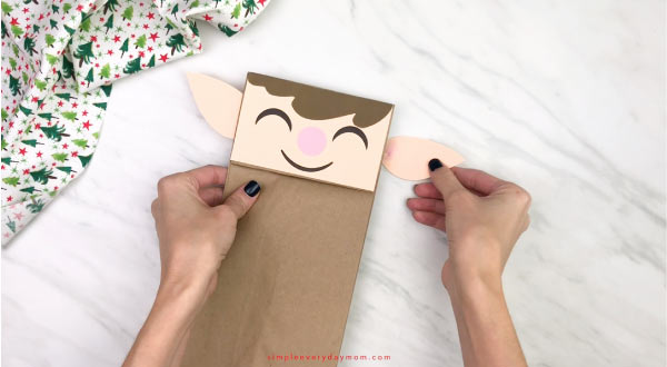 hand gluing ears to paper bag elf craft