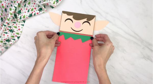 hand gluing shirt trim to paper bag elf craft