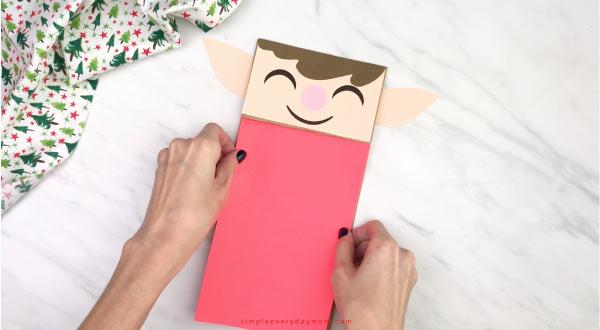 hand gluing shirt to paper bag elf craft
