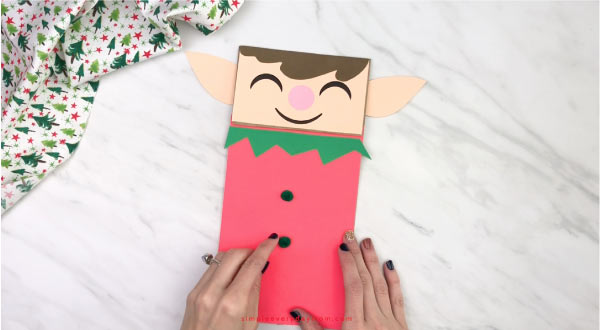 hand gluing pom pom buttons to paper bag elf craft
