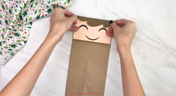hand gluing hair to paper bag elf craft