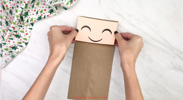 hand gluing face to paper bag elf craft