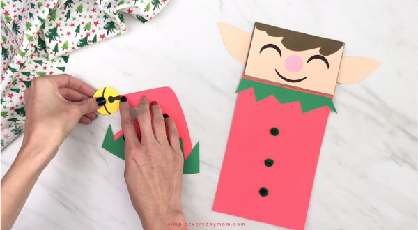 hands gluing paper bell to elf hat