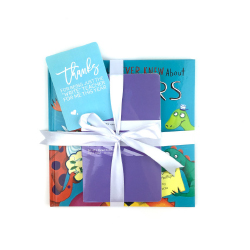 childrens book and purple journal wrapped up with teal gift tag