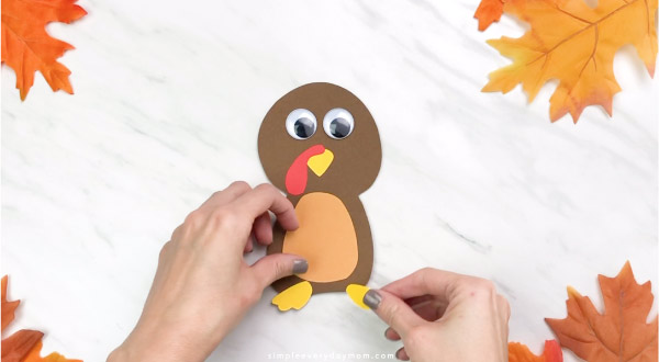 Hands gluing feet onto handprint turkey craft