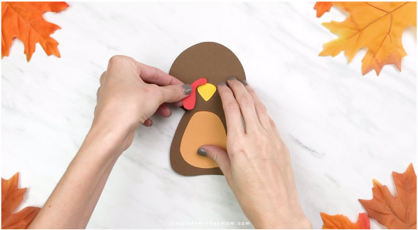 Hands gluing snood onto handprint turkey craft