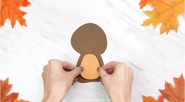 Hands gluing belly onto handprint turkey craft