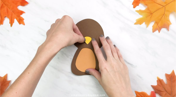 Hands gluing beak onto handprint turkey craft
