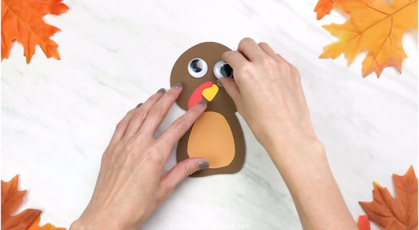 Hands gluing eyes onto handprint turkey craft