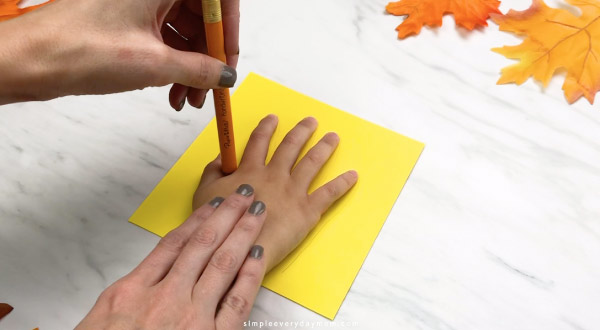 Adult hand tracing child hand on yellow paper