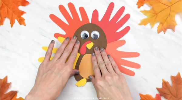 Hands gluing handprint feathers onto handprint turkey craft