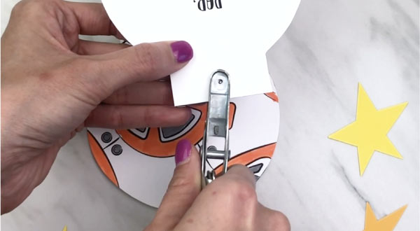 hand punching a hole in bb-8 card craft