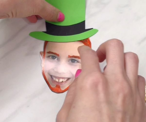 Hand gluing leprechaun hat on boy's photo