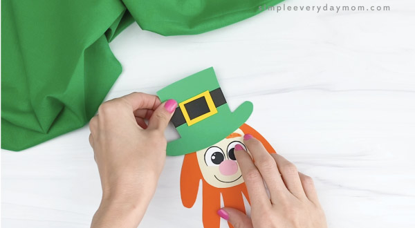 hand gluing hat to handprint leprechaun craft