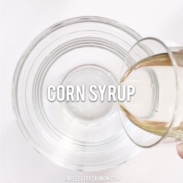 hand pouring corn syrup into bowl