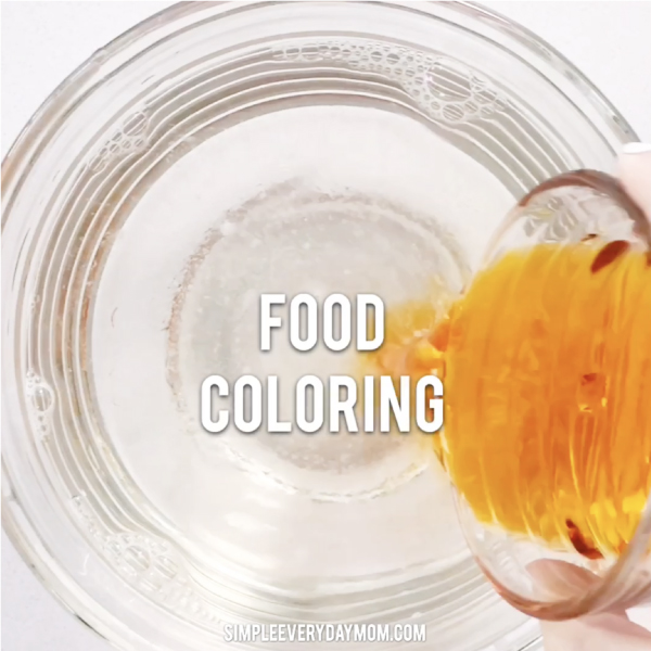 hand pouring food coloring into bowl