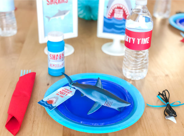 Shark Party Ideas   Create a simple but cool shark table setting with solid colored paper plates, a shark toy favor, napkins and some decorations. #partyideas #partyplanning #boysbirthday #birthdayparty