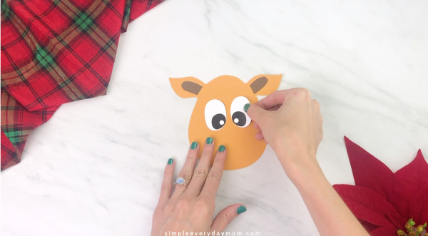 Hands gluing eyes to handprint reindeer craft