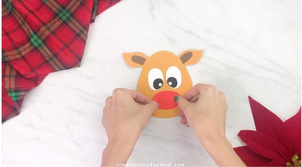 Hands gluing nose onto handprint reindeer craft