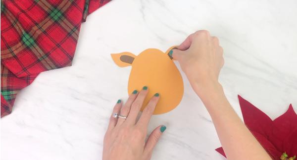 Hands gluing inner ear to handprint reindeer craft
