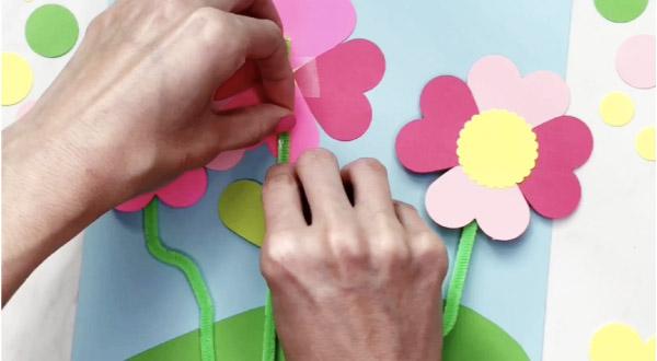 hand stretching glue dot on flower stem craft