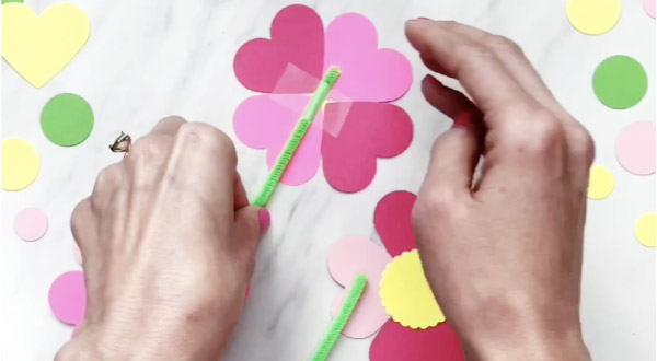hand taping pipe cleaner stem to paper flowers