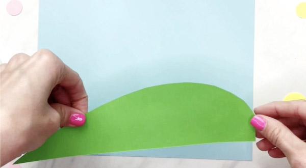 hand gluing grass to blue paper