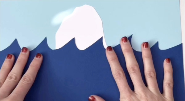 hand gluing wave to blue paper