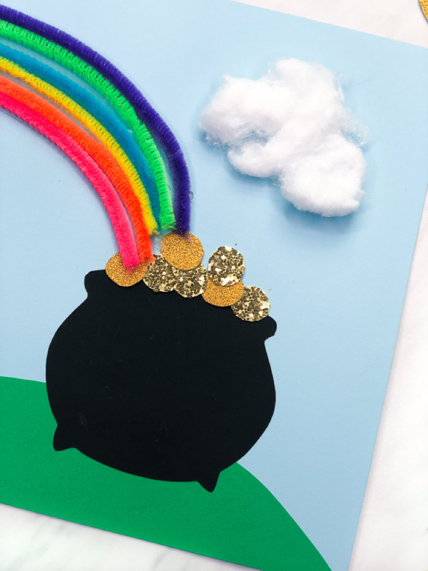 closeup of paper pot of gold with glitter coins and pipe cleaner rainbow