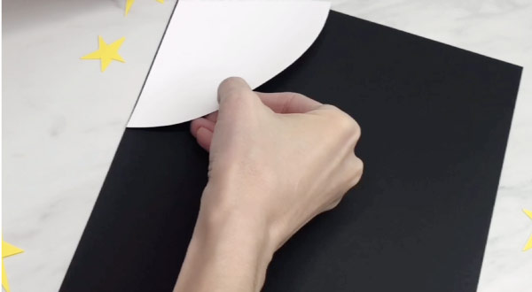hand gluing moon to black paper