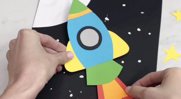 hand gluing rocket to space background