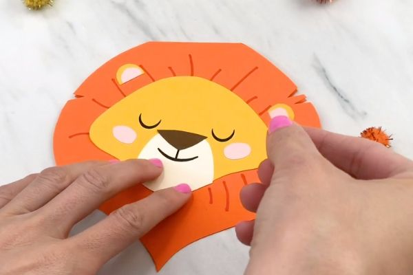 hands gluing on lion's ear to lion mane