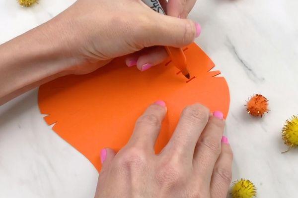 hands drawing on lion's mane marks with orange marker