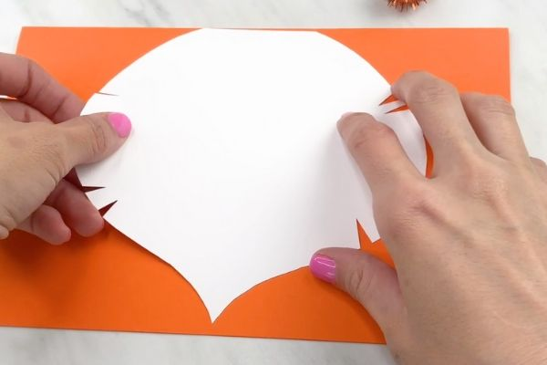 hand tracing lion mane on orange paper