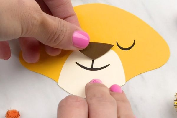 hand gluing brown nose to lion paper craft