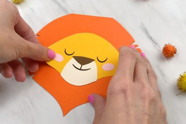 hands gluing on cheeks on paper lion craft