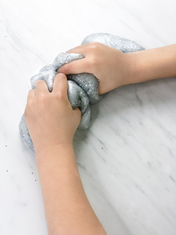 little kids hand squeezing silver slime