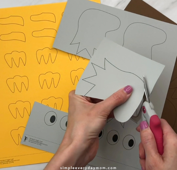 hand cutting out template from gray paper