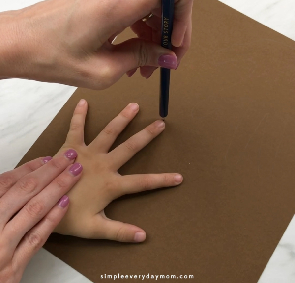 adult hand tracing child's hand on brown paper