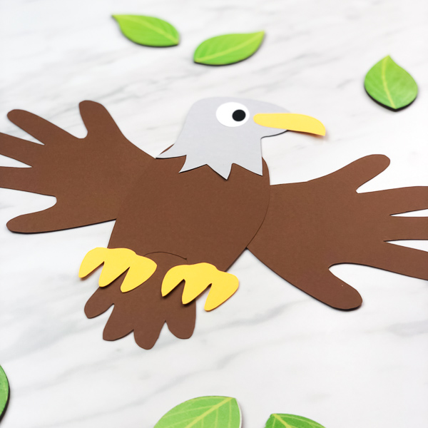 eagle paper craft surrounded by wooden leaves