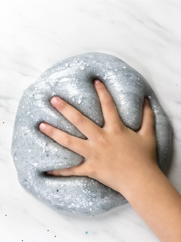 child's hand in silver glitter slime