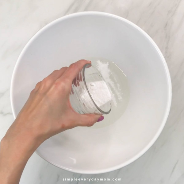 hand pouring baking soda into white bowl