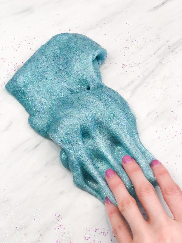 hand dragging finger into teal slime