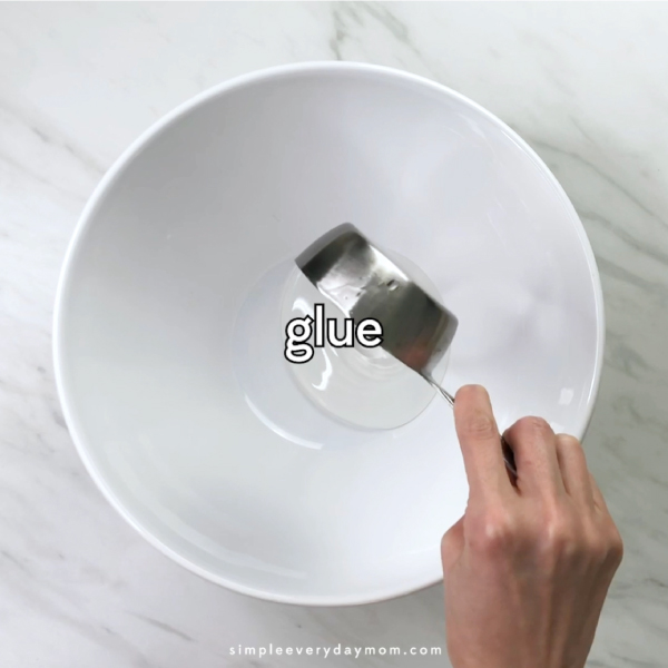hand pouring glue into white bowl