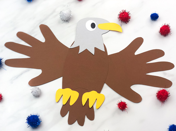 eagle kids craft surrounded by red white and blue pom poms