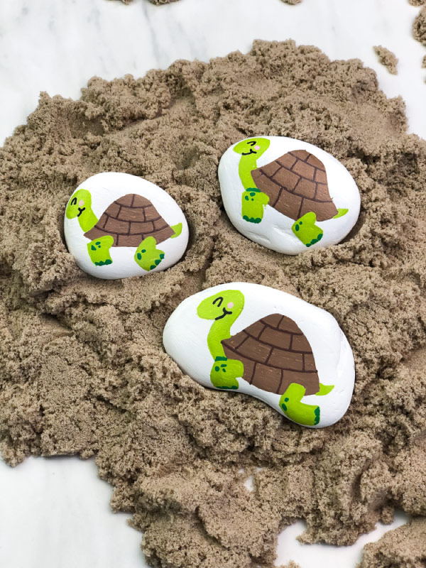 three turtle painted rocks on sand