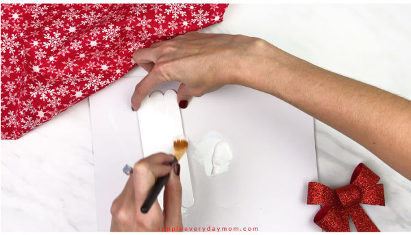 Hands painting craft sticks white