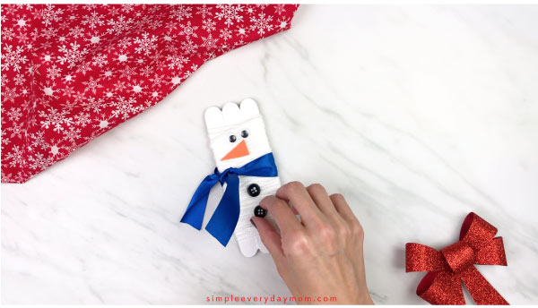 Hands gluing buttons on popsicle stick snowman