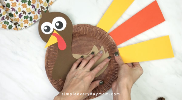 hands gluing feathers onto paper plate turkey craft
